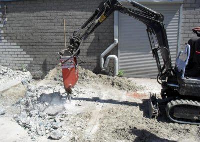 mini kraan sloopt beton vloer met hydraulische hamer