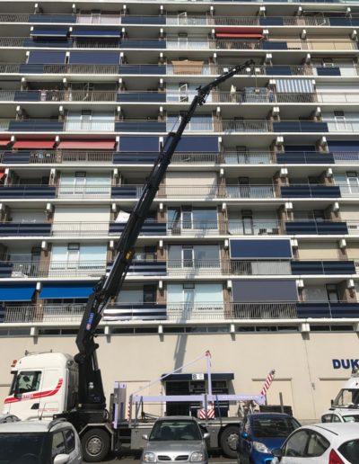 autolaadkraan bij flatgebouw maximaal