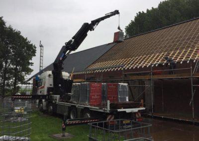 Autolaadkraan hijst pallet met dakpannen