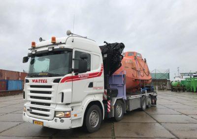 Autolaadkraan op industrieterrein met oranje valreddingsboot achterop