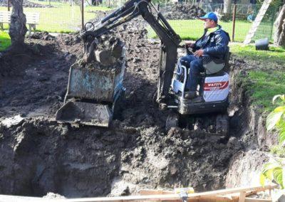 Minigraver met grond en puinbak buiten