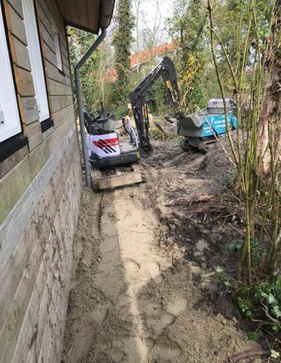 Minigraver in tuin met puinbak