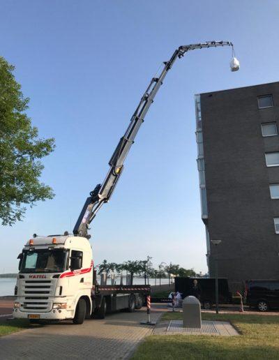 Autolaadkraan uitgeschoven boven gebouw